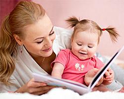 Eine Mutter liest ihrer kleinen Tochter aus einem Buch vor.