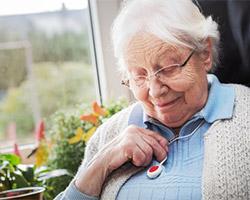 Eine ältere Dame sitzt im Sessel und hat den Notrufknopf umhängen.