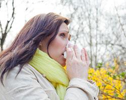 Eine Frau mit Heuschnupfen geht spazieren und putzt sich die Nase.