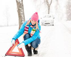 Eine Frau stellt ein Warndreieck auf der verschneiten Straße auf.